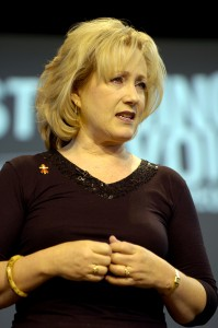 Rick Warren's wife, Kay Warren: speaking in church, wearing gold.
