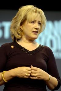 Rick Warren's wife, Kay Warren: speaking in church, wearing gold.